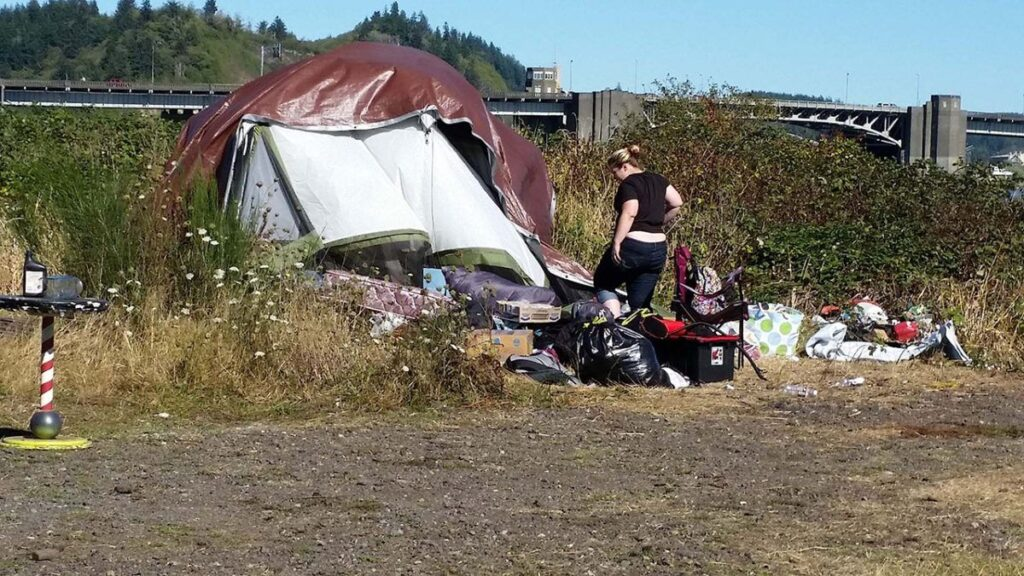 A camper cleans up at the Chehalis River encampment in Aberdeen, WA